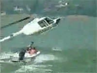 A helicopter attempts to tow a disabled boat